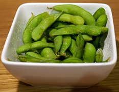 Boiled and salted edamame beans on pods